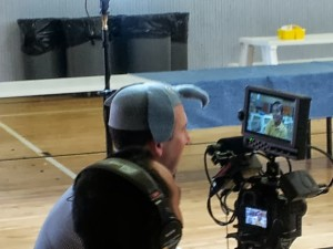 Brian Greenberg dons an elephant hat while interviewing a student at KIPP LA. Photo by Michael Horn.