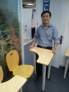 Duy Phan, CFO of Yola Institute, showing off the modular desks he and his team designed that allow Yola to create a variety of arrangements for individual and group learning. Photo by Michael B. Horn